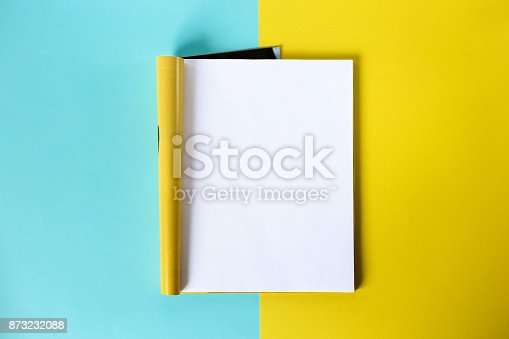 istock Mock-up magazine and catalog concept. Top view. Open page of the magazine on a blue and yellow background. Copy space. Template 873232088