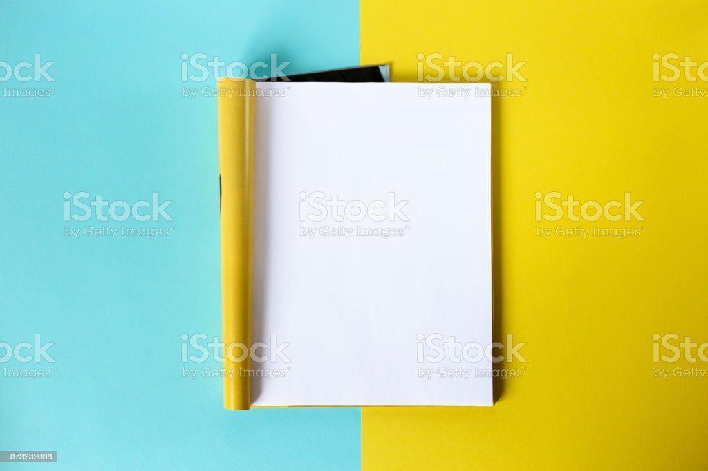 Mock-up magazine and catalog concept. Top view. Open page of the magazine on a blue and yellow background. Copy space. Template stock photo