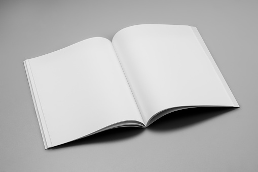 Mock-up magazine, book or catalog on gray table. Blank page or notepad on solid background. Blank page or notepad for mockups or simulations.