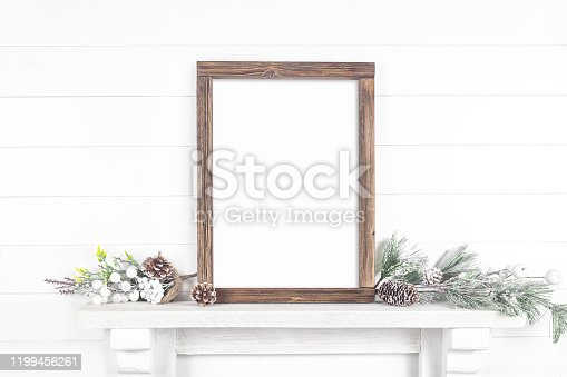 A mock-up of a frame made of rough wood on a light background with a pine branch on the mantelpiece