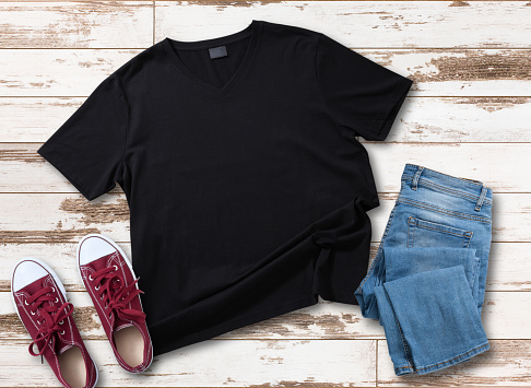 istock Mockup of blank black t shirt and jeans jacket, red sneakers and denim pants on white wooden background. Shirt design for man. Flat lay, top view. 1184036419