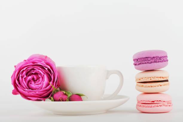mock-up der kaffeetasse mit rosenblüte und stapel von makronen. weißen hintergrund für text. - rosentorte stock-fotos und bilder