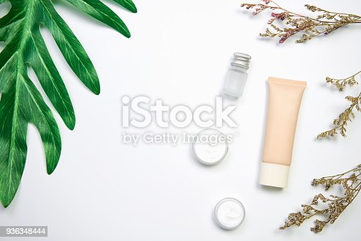 927626522 istock photo Mockup of cosmetic cream bottle, Blank label package and ingredients on a green leaves background. Concept of natural beauty products. 936348444