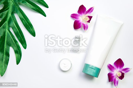 927626522 istock photo Mockup of cosmetic cream bottle, Blank label package and ingredients on a green leaves background. Concept of natural beauty products. 936348446