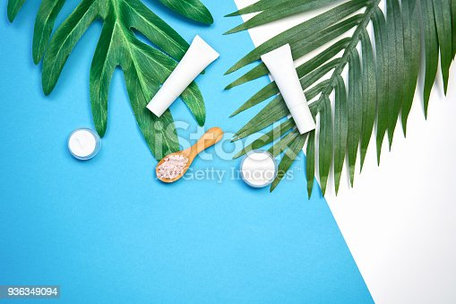 927626522 istock photo Mockup of cosmetic cream bottle, Blank label package and ingredients on a green leaves background. Concept of natural beauty products. 936349094