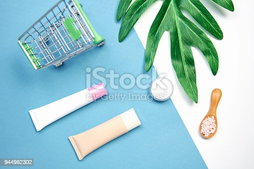 927626522 istock photo Mockup of cosmetic cream bottle, Blank label package and ingredients on a green leaves background. Concept of natural beauty products. 944962302