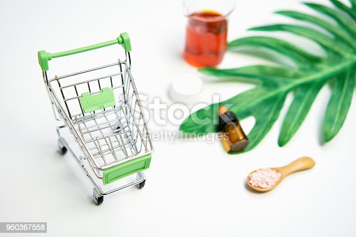 927626522 istock photo Mockup of cosmetic cream bottle, Blank label package and ingredients on a green leaves background. Concept of natural beauty products. 950367558