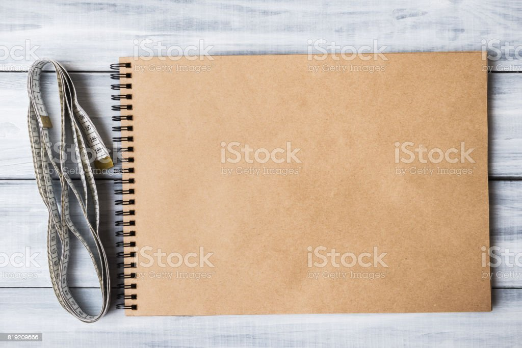 Mock-up of empty note pad with measuring tape over  wooden background stock photo