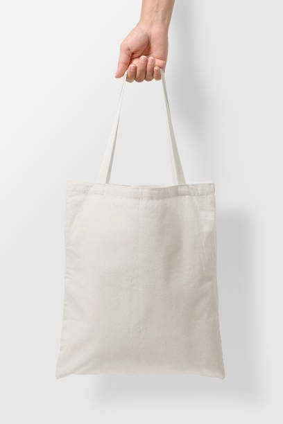 mockup of female hand holding a blank tote canvas bag on light grey background. - tote bag imagens e fotografias de stock