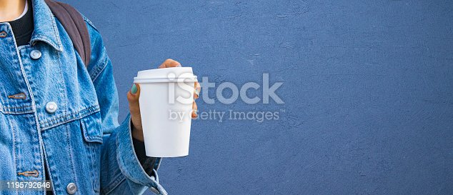 Mockup of female hand holding a Coffee paper cup isolated blue background
