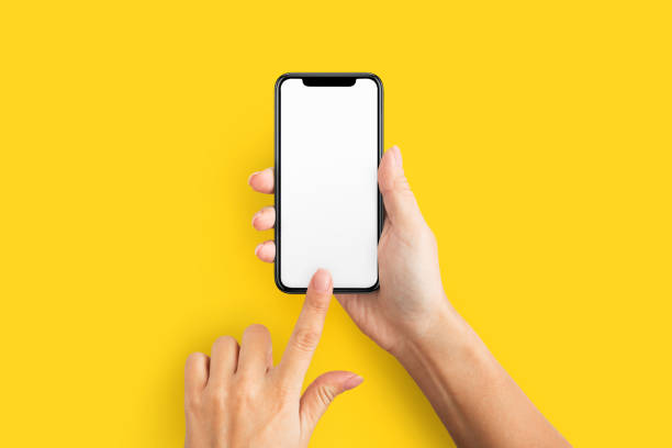 Mockup of female hand holding cell phone with blank screen Mockup of female hands touching cell phone with blank screen on yellow background. phone stock pictures, royalty-free photos & images
