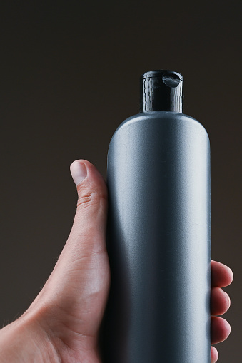 1151624350 istock photo mockup of gray plastic bottle in hands on a dark background 1264329061