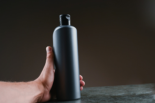 1151624350 istock photo mockup of gray plastic bottle in hands on a dark background 1264331967