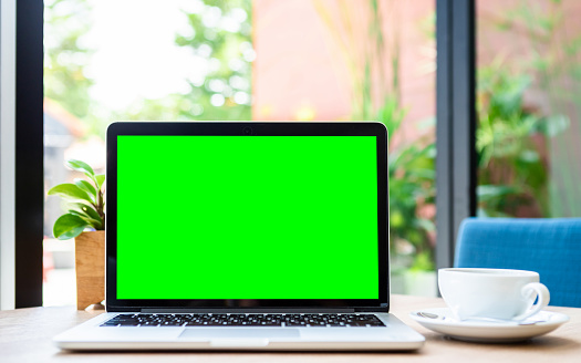 Mockup of laptop computer with empty screen with coffee cup on table of the coffee shop background,green screen