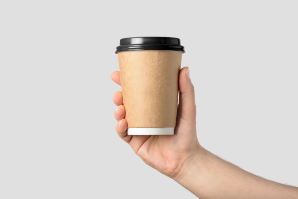 mockup of male hand holding a coffee paper cup isolated on light grey background. - paper coffee cup stock photos and pictures