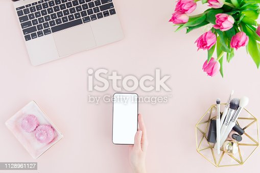 Mockup of mobile phone with blank copy space screen in female hand. Flat lay, top view pastel color workspace