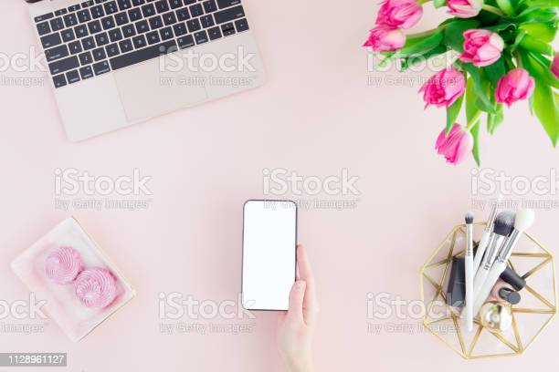 Photo of Mockup of mobile phone with blank copy space screen in female hand. Flat lay, top view pastel color workspace