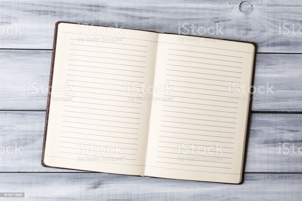 Mock-up of open blank note pad over light wooden background stock photo