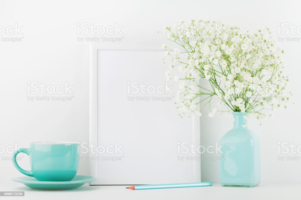 Mockup of picture frame decorated flowers in vase and coffee cup. Website design concept.