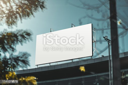 An empty huge poster mockup on the roof of a mall; white template placeholder of an advertising billboard on the rooftop of a modern building framed by trees; blank mock-up of an outdoor info banner