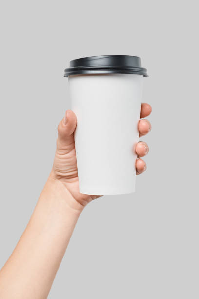 Mockup of women's hand holding white paper large size cup with black cover stock photo