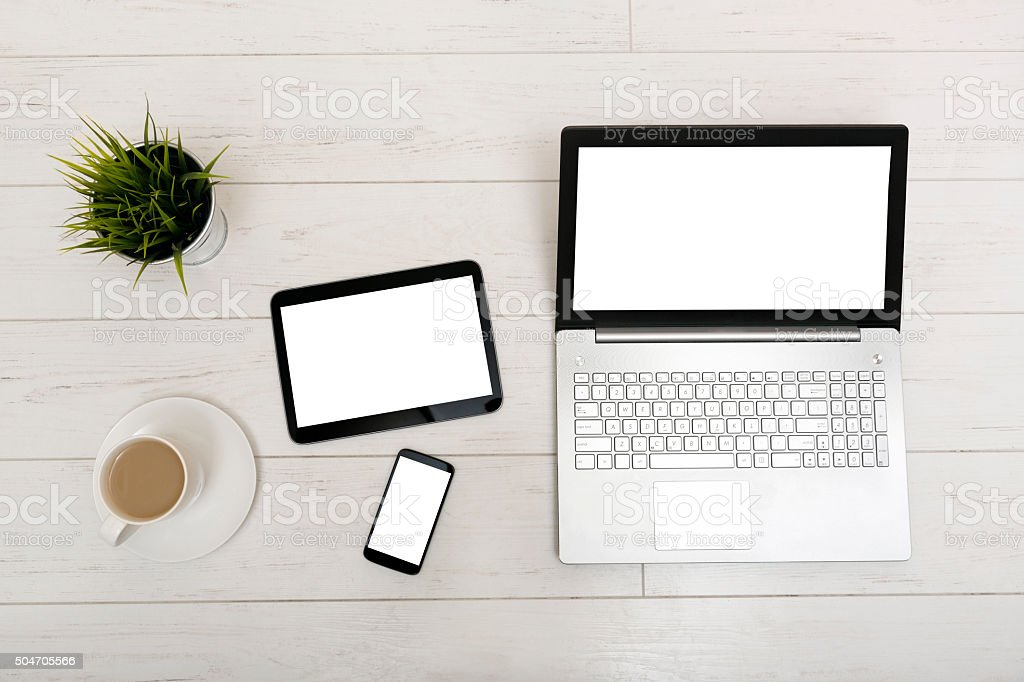 mockup on a table with blank laptop, tablet and smartphone stock photo