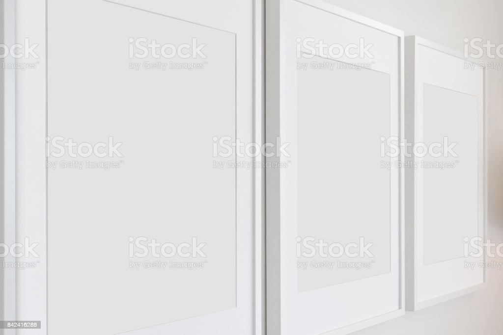 Set of blank wall-hung picture frames in a home. The picture frames...