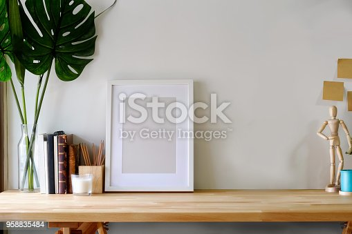 istock Mockup poster on wooden table with copy space. 958835484