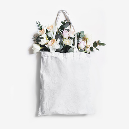 Mock-up scene of blank shopping canvas tote bag with pink tulips, daffodils flowers and eucalyptus isolated on white backfound. Spring, Easter sale. Eco friendly, zero waste concept. Flat lay, square.