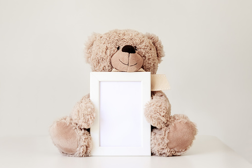istock Mockup. Soft beige teddy bear toy holding white clean mock up frame with copy space sitting at light grey background. Empty space. Baby children concept. 1178761413