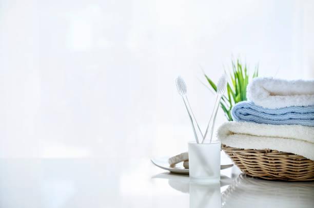 Mockup toallas suaves en la cesta y cepillo de dientes sobre fondo blanco. - foto de stock