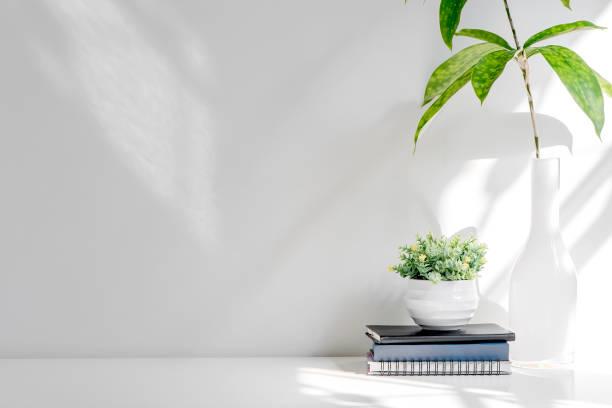 Pila de Mockup de libro y planta de casa en mesa de madera blanca, copiar espacio para la exhibición del producto o montaje. - foto de stock