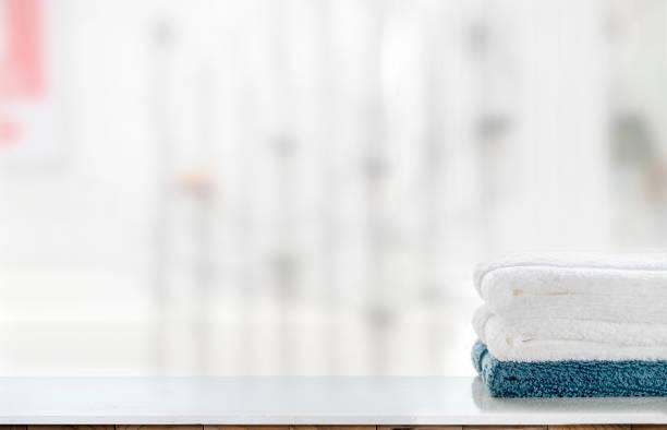 Pila de toques de toallas limpias sobre mesa blanca y fondo borroso. - foto de stock