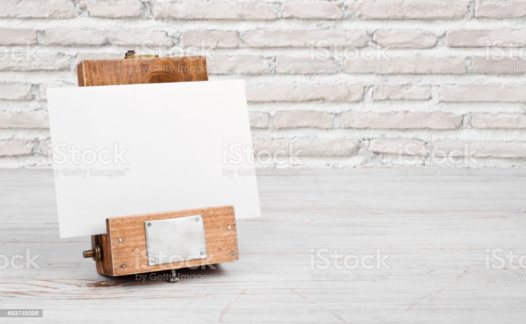 Mockup stand with paper on table over abstract brick wall stock photo