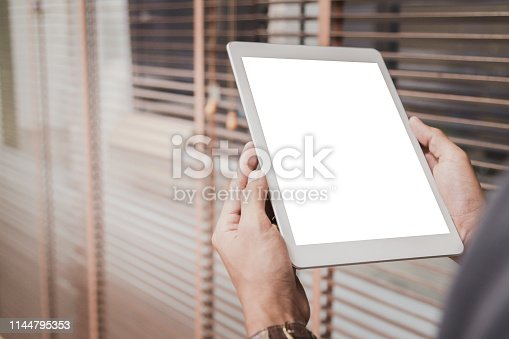 Mockup tablet on businessman hands empty display on home table with blur background. - Image - Image