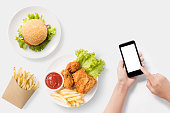 Design concept of mockup Using smartphone with burger, french fries, fried chicken set isolated on white background. Copyspace for text and logo. Clipping Path included on white background.