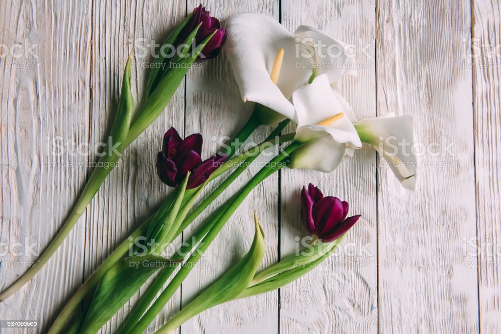 Mockup. White calla Flowers on a white wooden background. Flat lay,...