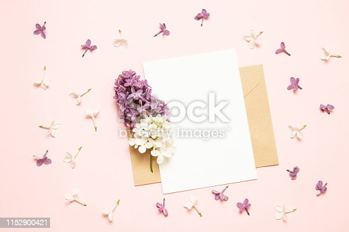 680461500 istock photo Mockup white greeting card and envelope with lilac branches on a light background 1152900421