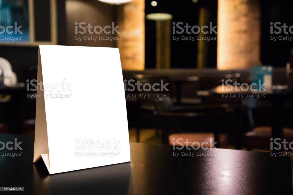 Mockup white label menu frame on table with cafe restaurant interior background stock photo