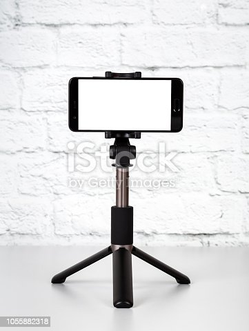 Mockup with smartphone on a tripod with empty screen on office table and brick wall background. Cope space