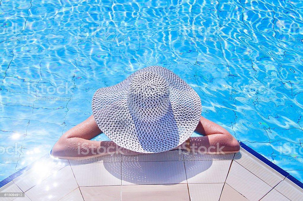 Młoda kobieta z biały kapelusz odpoczynku w basenie – zdjęcie