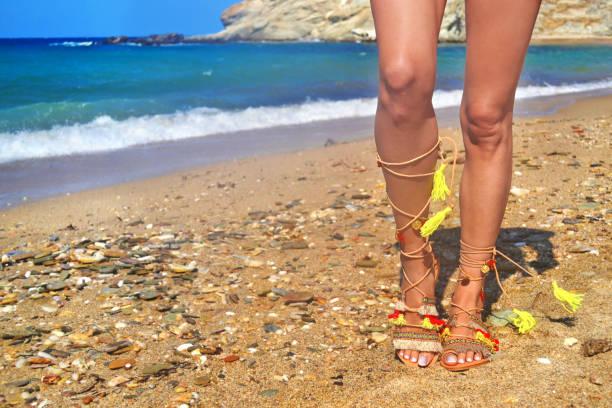 model advertises bohemian greek sandals at the beach stock photo