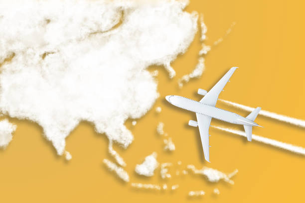 Model airplane design miniature yellow background fluffy clouds in the shape of continent Asia. The idea of tickets for the trip, traveling by plane, new discoveries, summer holidays stock photo