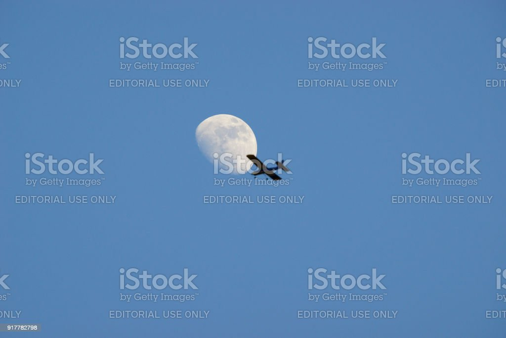 Model airplane flying over the moon.