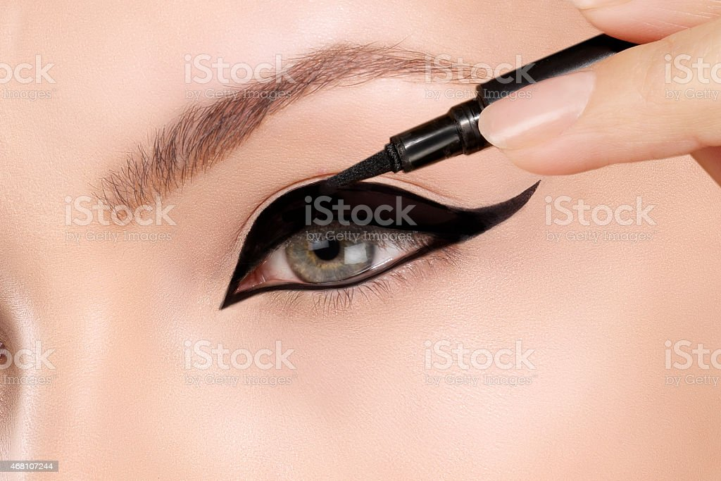 Model applying black eye liner stock photo