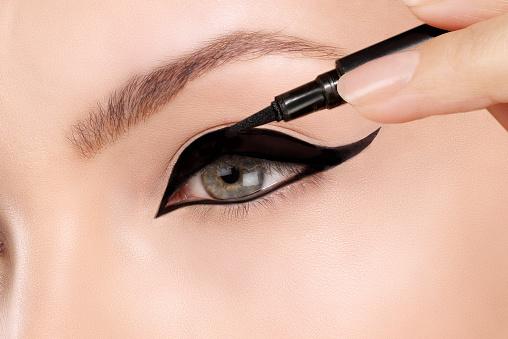 Model applying black eye liner stock photo