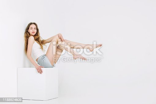 Model beautiful young girl with blonde hair and blue eyes in t-shirt and shorts fashionable on white cube in Studio