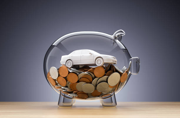 Model Car on money inside transparent piggy bank stock photo