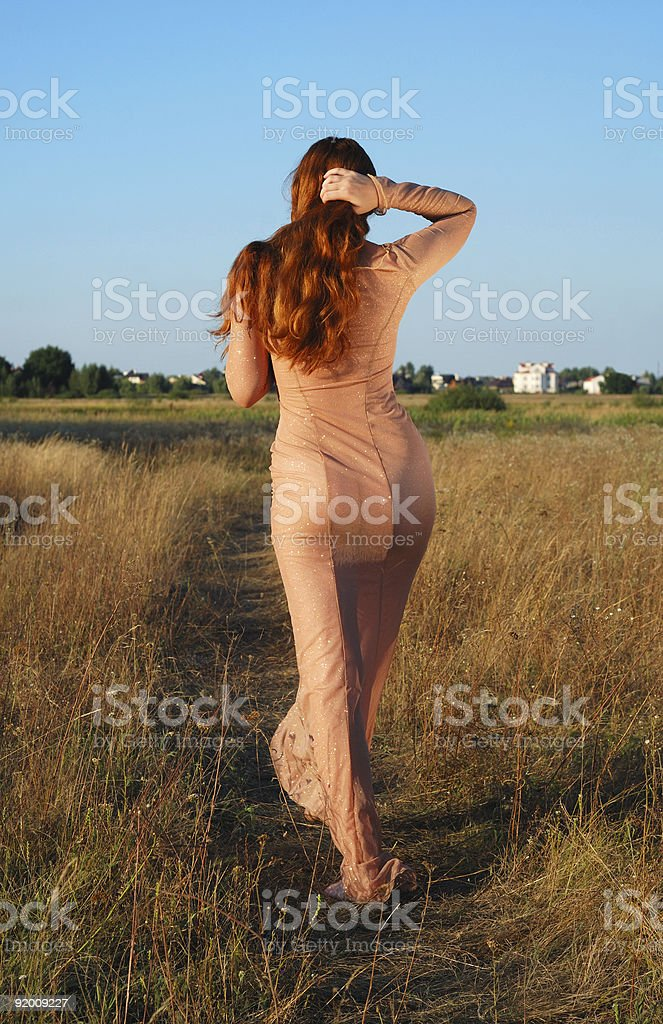 Model going on path in long beige dress royalty-free stock photo