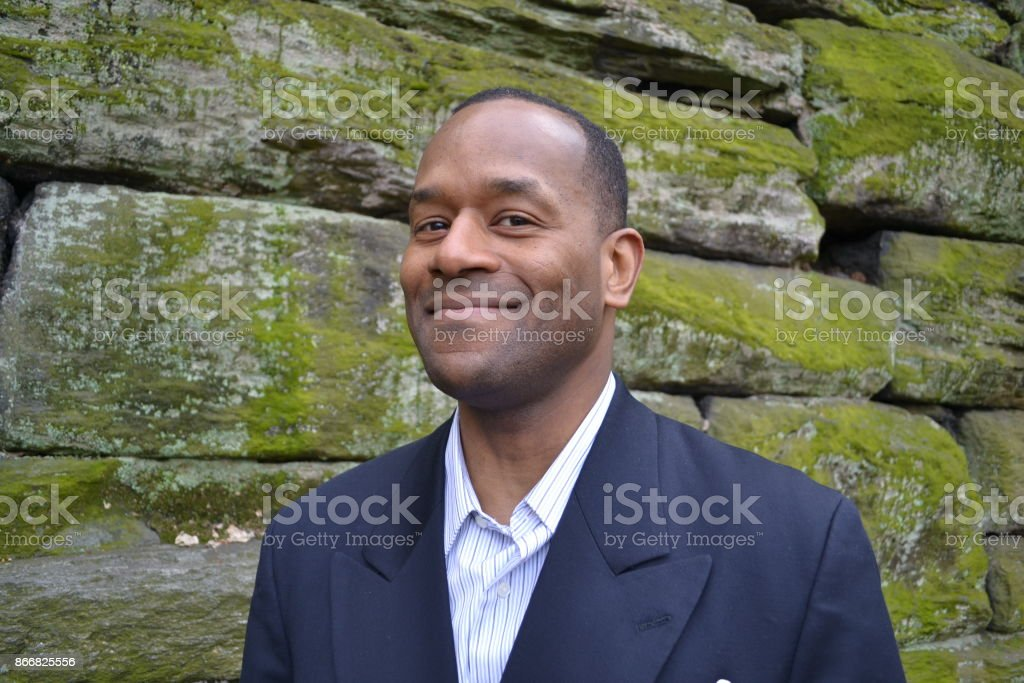 Model happy & smiling wearing a business suit ; brick wall stock photo